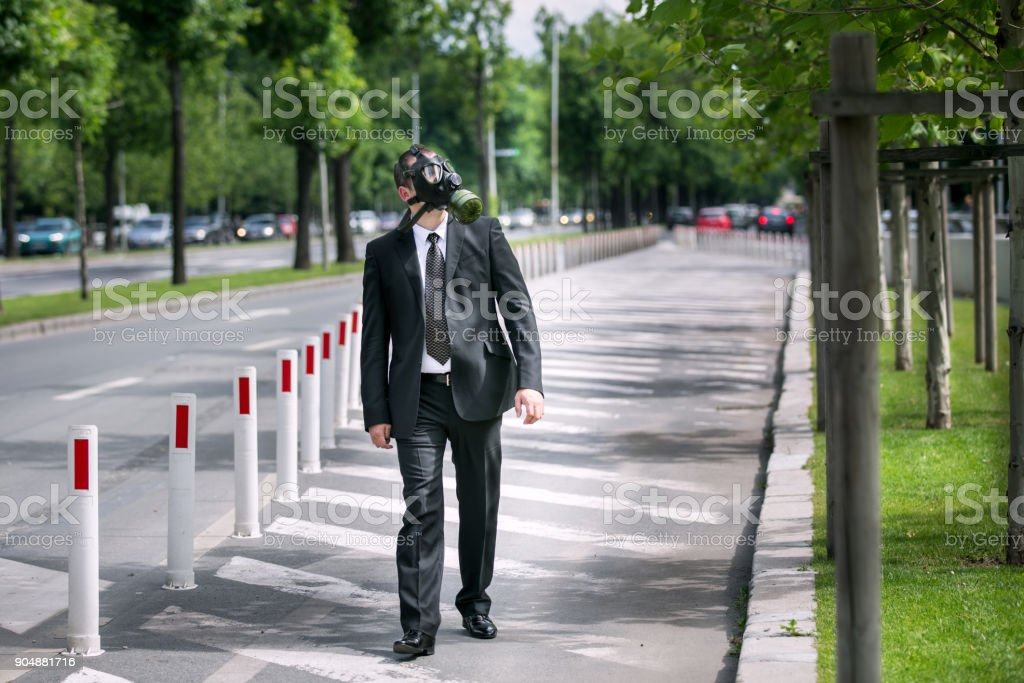 Businessman wearing a gas mask looking to the sky stock photo