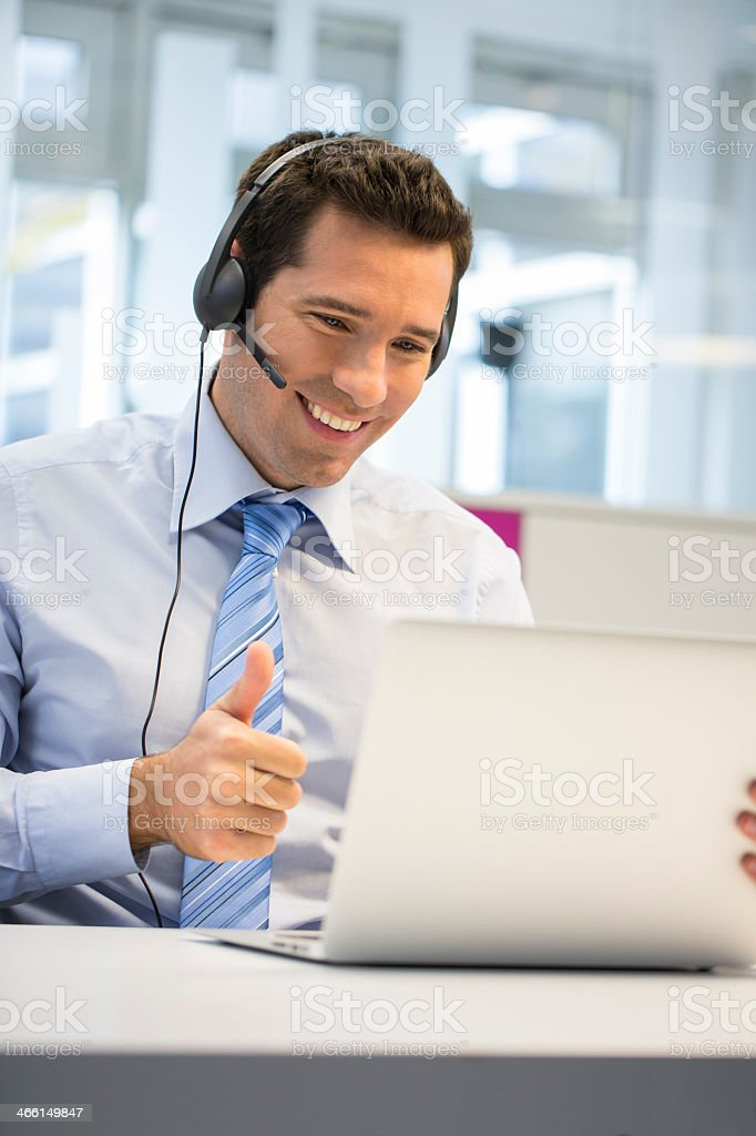 Businessman wearing a headset smiling stock photo