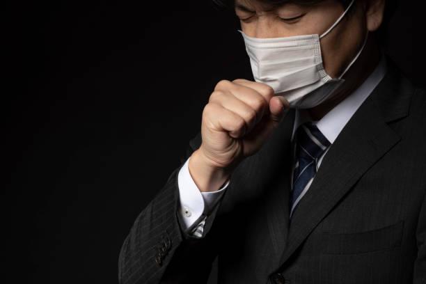 医療マスクを身に着けているビジネスマン - くしゃみ 日本人 ストックフォトと画像