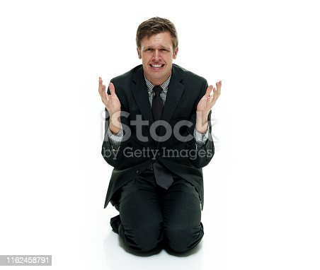 Businessman wearing a suit with necktie on white background sitting on floor