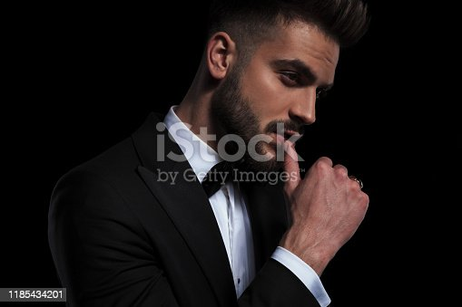 side view of a young businessman wearing black tuxedo seductively touching his lips on black studio background