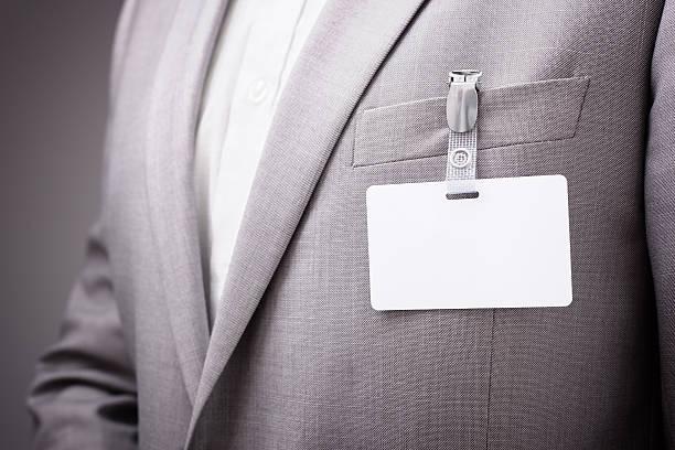 hombre de negocios usando tarjeta de nombre en blanco - insignia símbolo fotografías e imágenes de stock