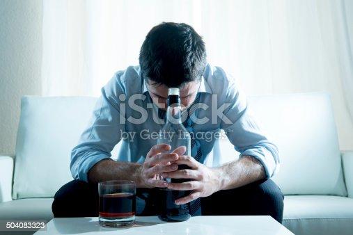 istock Businessman wearing blue shirt drunk at desk on white background 504083323