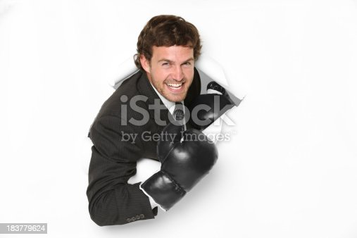 160558362 istock photo Businessman wearing boxing gloves breaking through hole 183779624