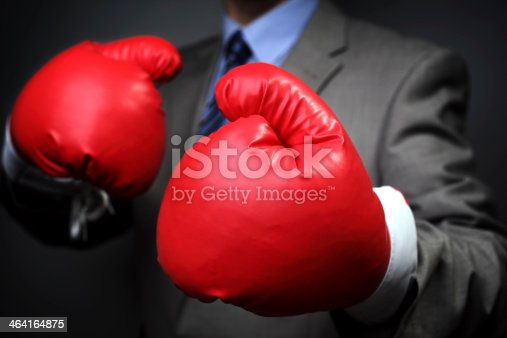 464164875 istock photo Businessman wearing boxing gloves 464164875