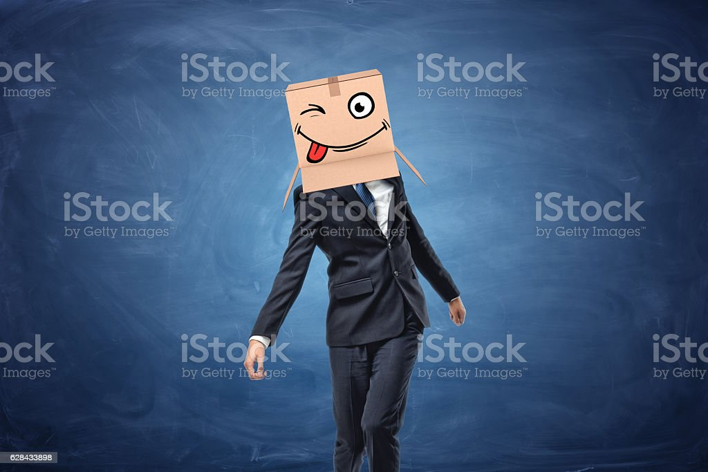 Businessman wearing cardboard box with drawn winking face on his stock photo
