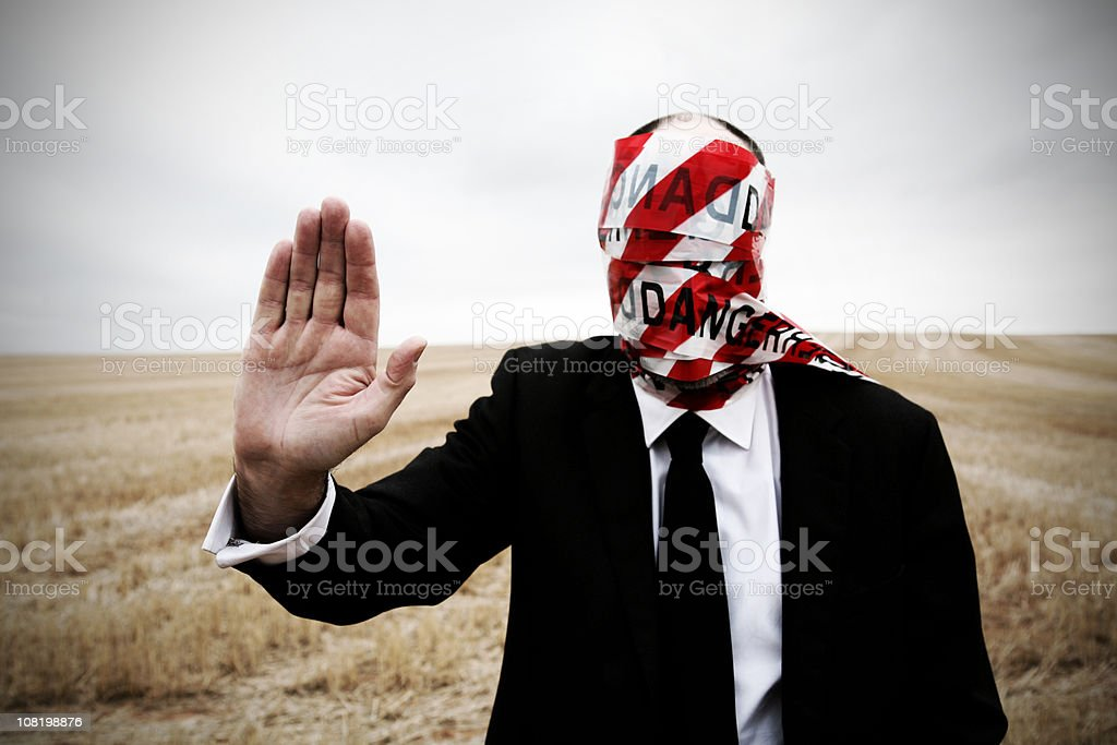 Businessman Wearing Danger Tape Around Face and Holding Hand Up royalty-free stock photo