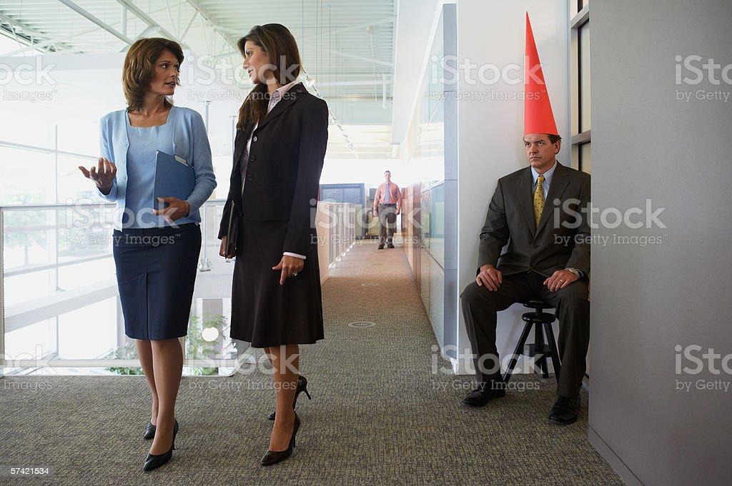 Businessman wearing dunce cap stock photo