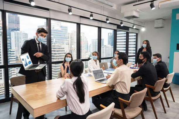 Businessman wearing face mask with presentation of business plan on laptop, corporate business meeting in modern office stock photo