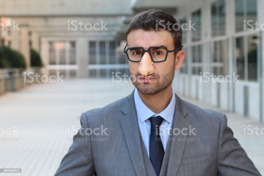 Businessman wearing fake nose-glasses combo stock photo
