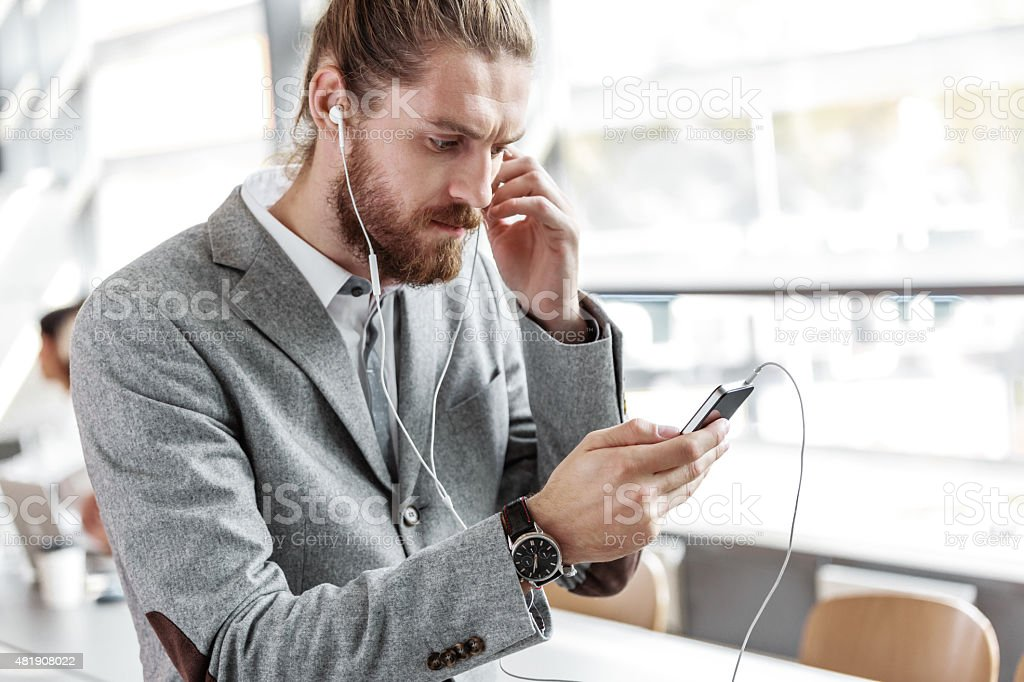 Businessman wearing grey suit and earphone using smart phone Bearded businessman wearing grey suit and earphone using smart phone in an office. 2015 Stock Photo
