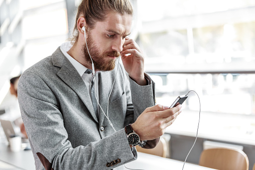 Businessman Wearing Grey Suit And Earphone Using Smart Phone Stock Photo - Download Image Now
