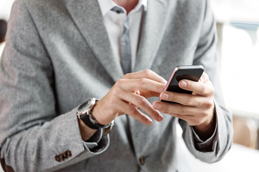 Businessman Wearing Grey Suit Using Smart Phone Stock Photo - Download Image Now