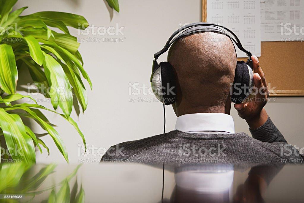 Businessman wearing headphones stock photo