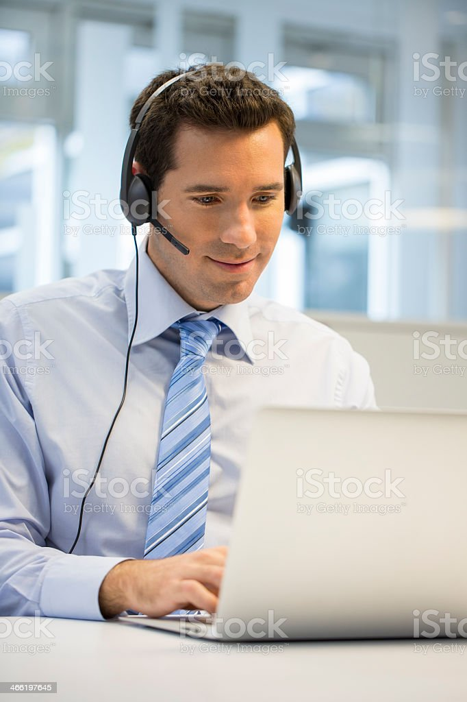 Businessman wearing headset at office on phone using Skype stock photo