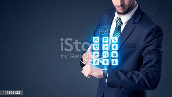 Businessman wearing smartwatch with application icons.