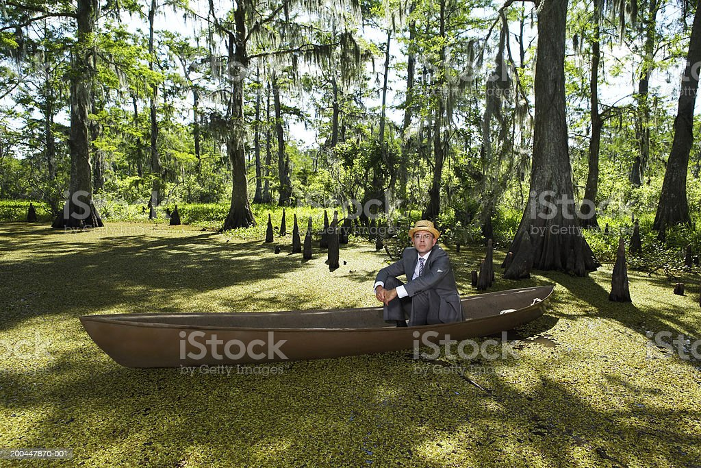 Businessman wearing straw hat sitting in boat in swamp, portrait stock photo