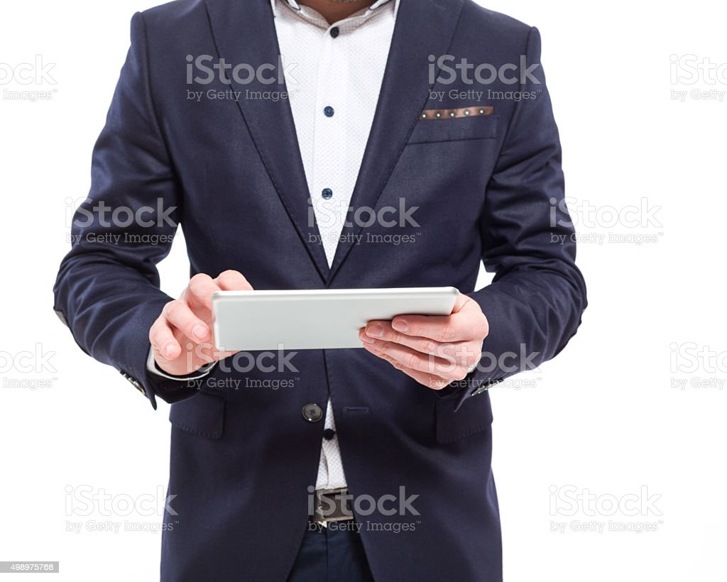 Businessman wearing suit using a digital tablet Part of elegant businessman standing against white background and using a digital tablet. Close up of hands. 2015 Stock Photo
