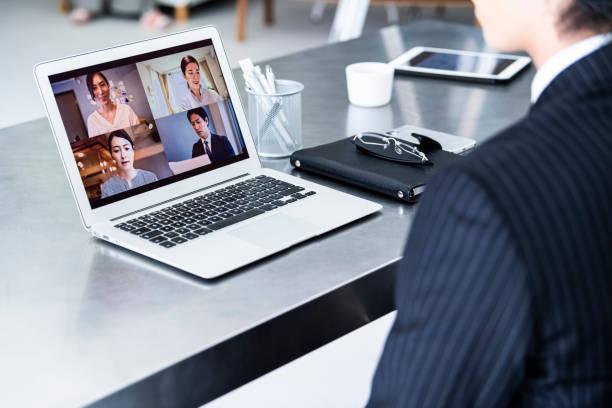 スーツを着たビジネスマンがオフィスでオンライン会議をしています - リモート ストックフォトと画像