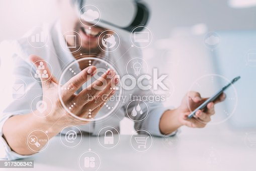 917307226 istock photo businessman wearing virtual reality goggles in modern office with mobile phone using with VR headset with screen icon diagram 917306342