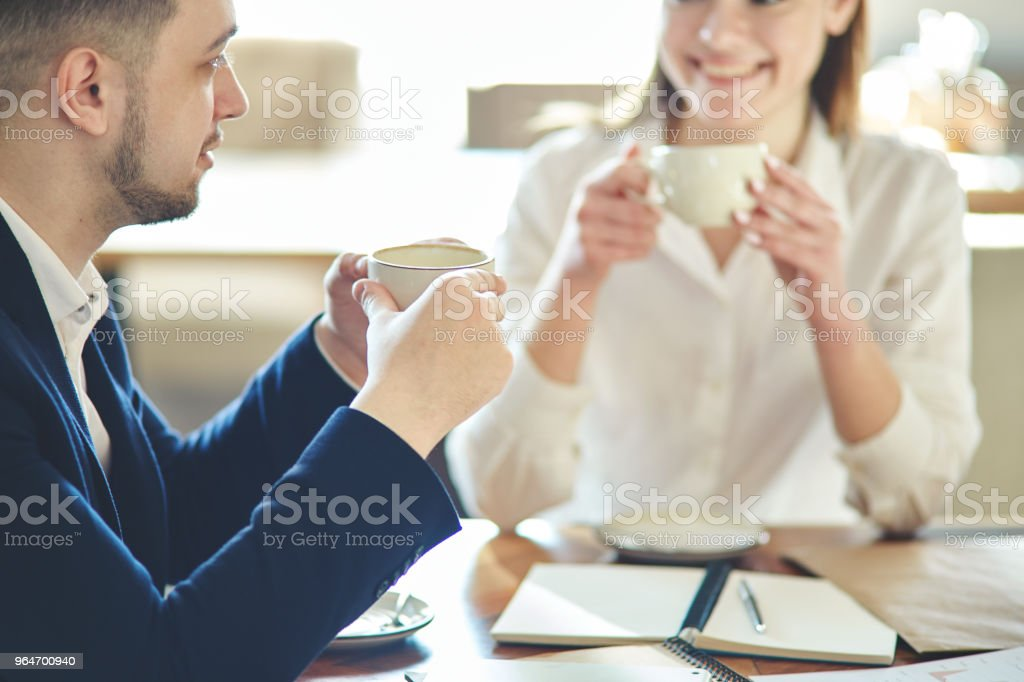 Businessman wearing white shirt and jacket talking to defocused female business partner during meeting in cafe. Business people drinking coffee and having friendly discussion royalty-free stock photo