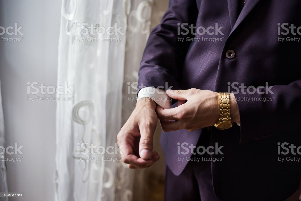 Businessman wears a jacket,male hands closeup,groom getting ready in the morning before wedding ceremony stock photo