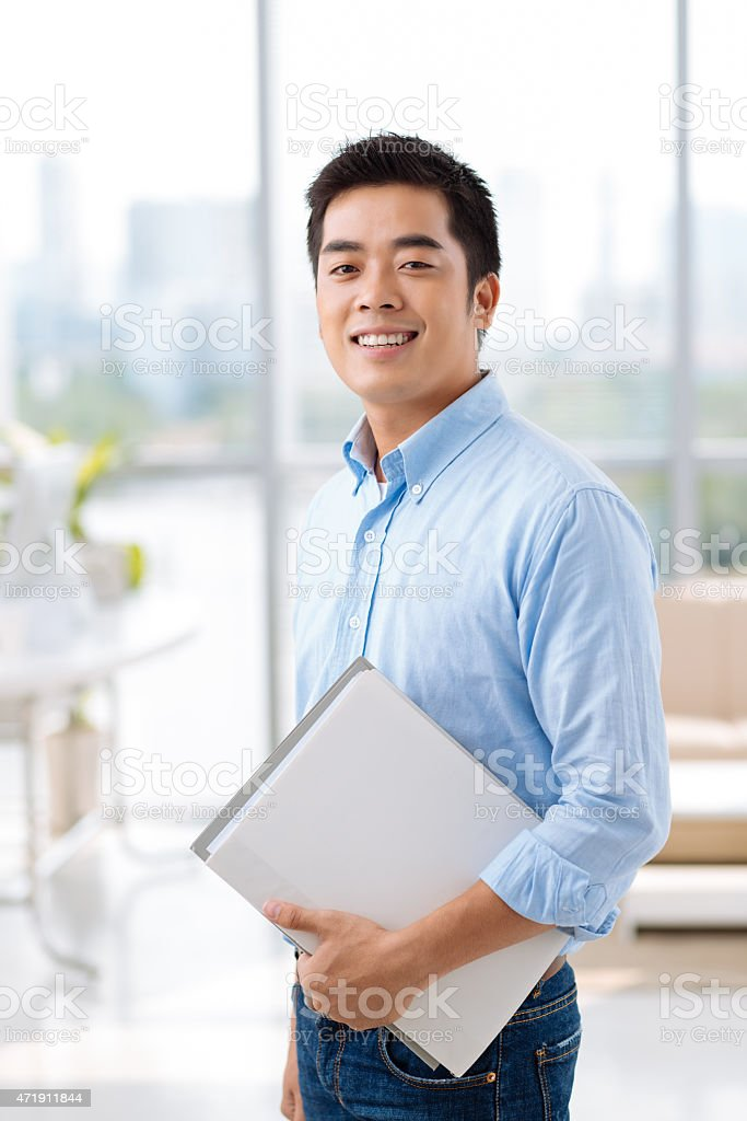 A businessman who is holding several documents  stock photo