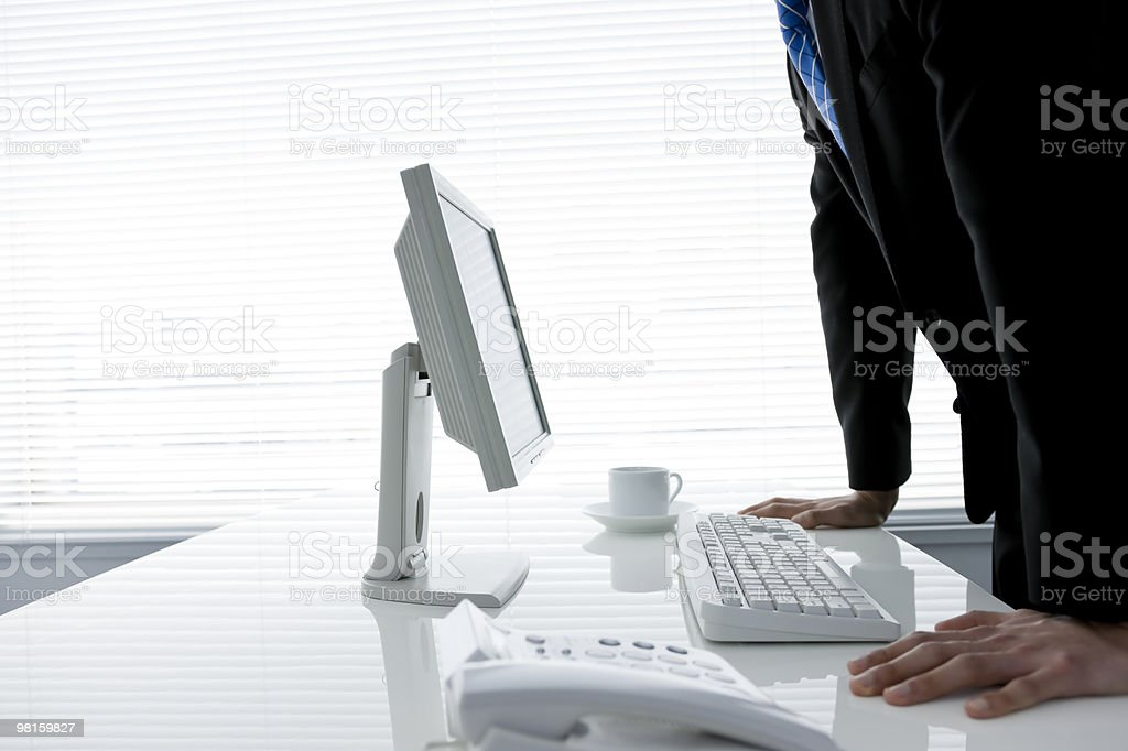Businessman who stands in front of office desk royalty-free stock photo