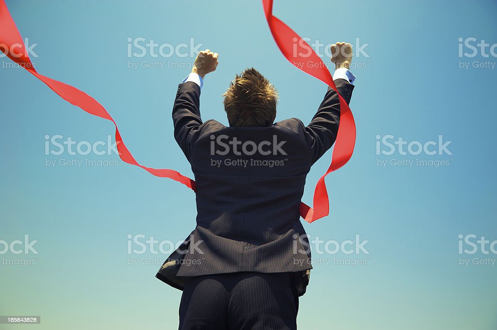 Businessman Winning Success Outdoors at Red Finish Line Blue Sky stock photo