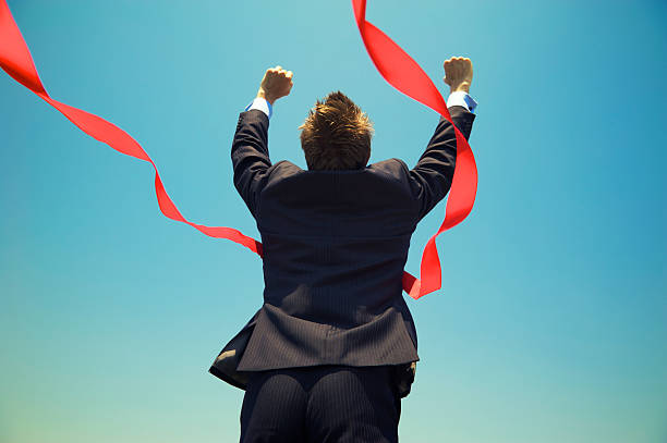 businessman winning success outdoors at red finish line blue sky - finishing stock photos and pictures