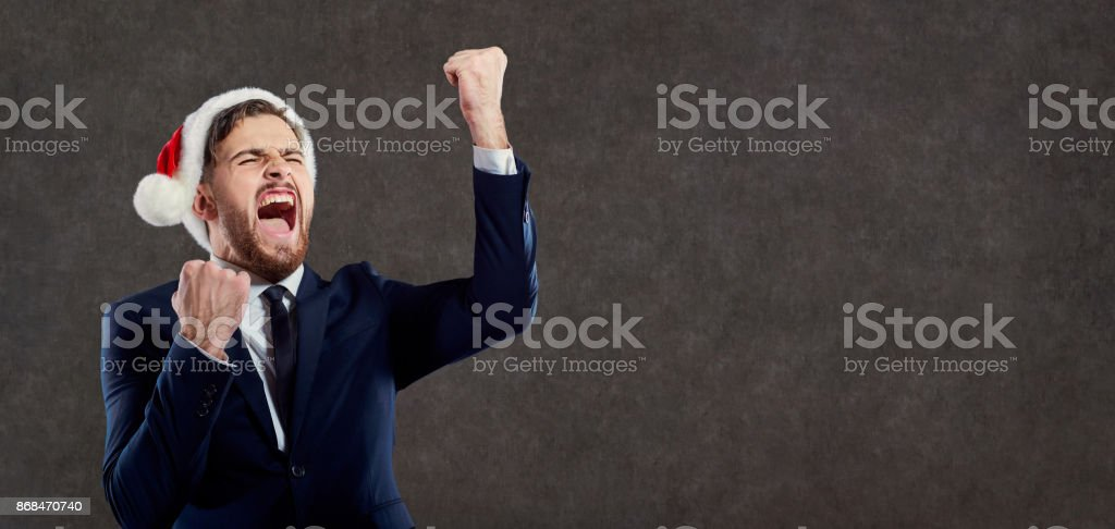 Businessman with a beard in a Santa Claus hat shouts. stock photo