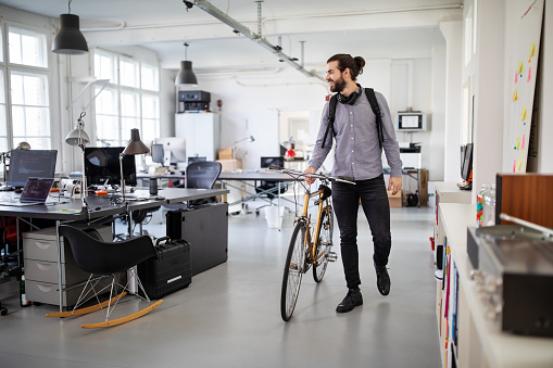 Businessman with a bicycle in office. Business professional going home after work.