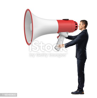 istock Businessman with a big megaphone isolated on white background 1165465832