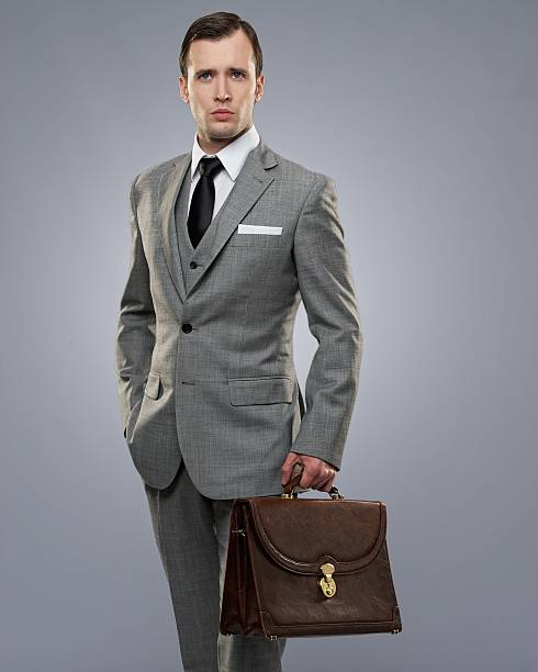 Businessman with a briefcase isolated on grey. stock photo