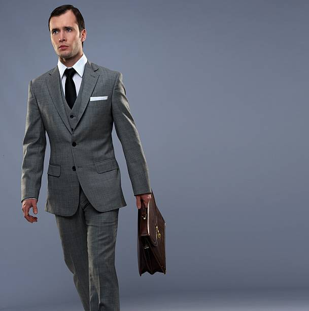 Businessman with a briefcase isolated on grey stock photo