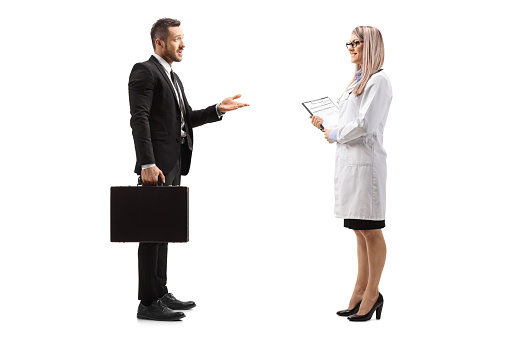 Full length profile shot of a businessman with a briefcase talking to a young female doctor isolated on white background