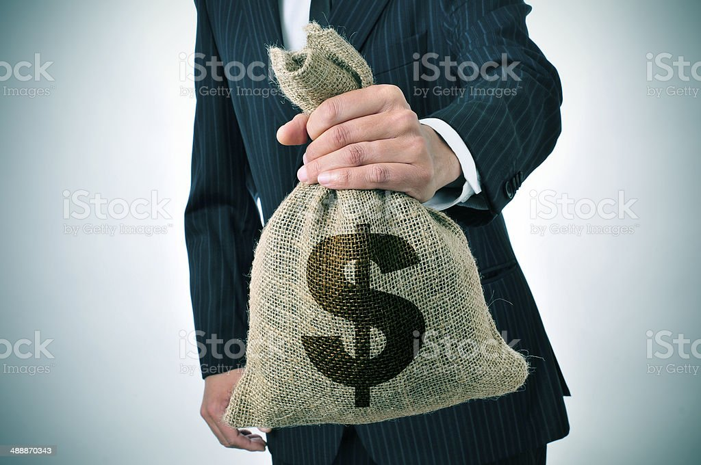 businessman with a burlap money bag stock photo