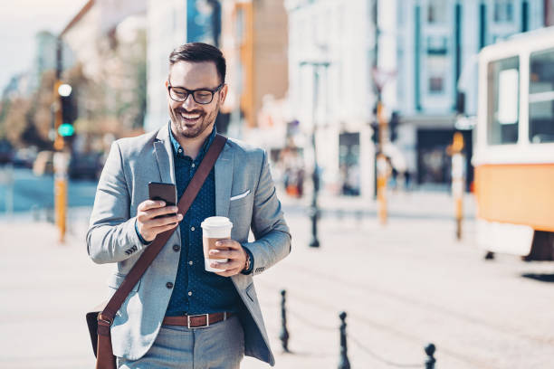 Businessman with a cell phone on the street stock photo