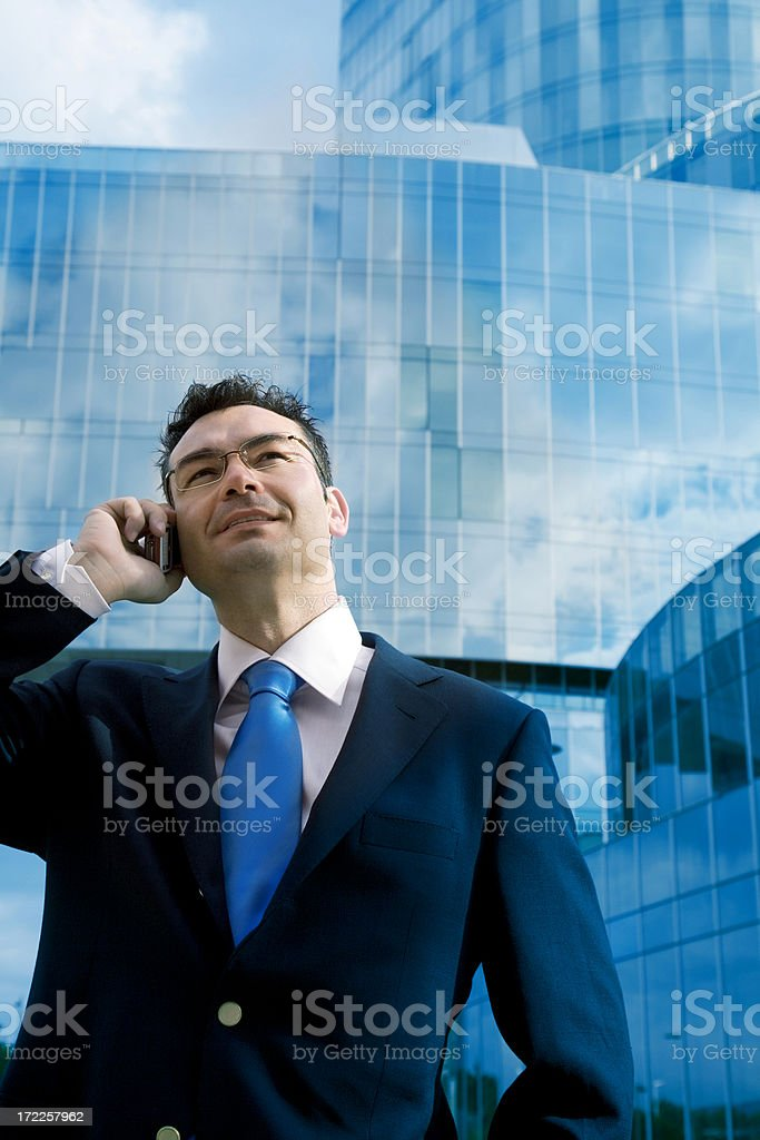 Businessman with a cellphone outside modern building royalty-free stock photo