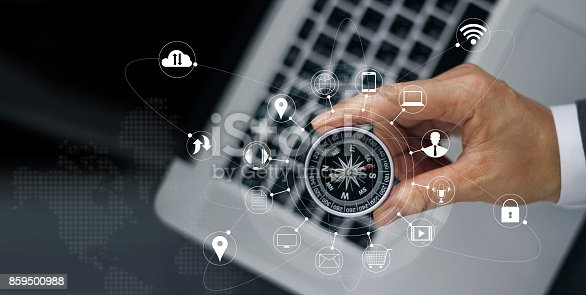 istock Businessman with a compass holding in hand on laptop and icon customer network connection on screen, m-banking and omni channel 859500988