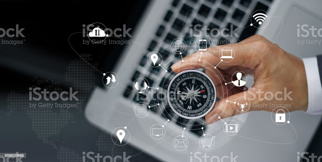 Businessman with a compass holding in hand on laptop and icon customer network connection on screen, m-banking and omni channel stock photo