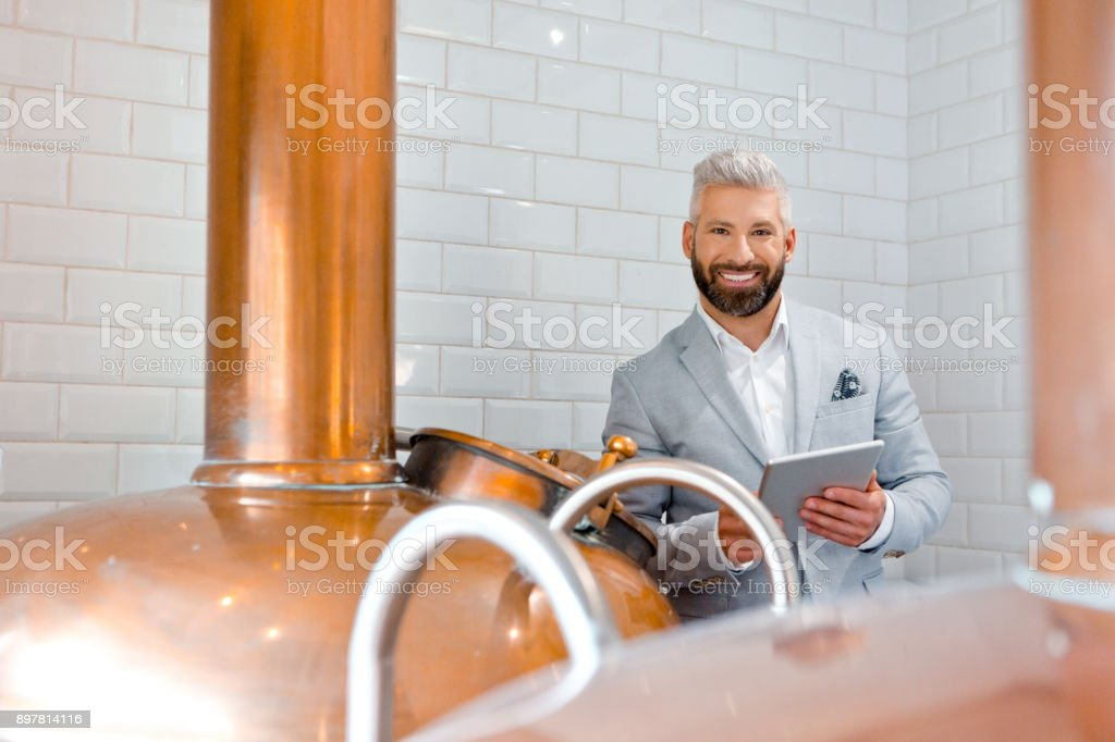 Businessman with a digital tablet at micro brewery Micro brewery owner with a digital tablet in fermenting section of beer manufacturing factory. Handsome man in suit using digital tablet while standing by a copper vat in brewery. Adult Stock Photo