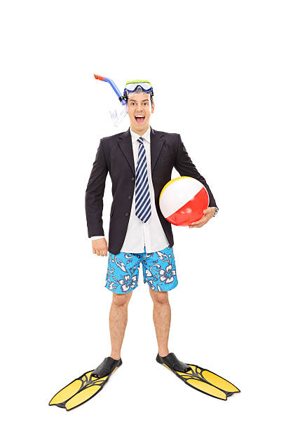 Businessman with a diving mask holding a beach ball Full length portrait of a young businessman with a diving mask holding a beach ball and looking at the camera isolated on white background diving flipper stock pictures, royalty-free photos & images