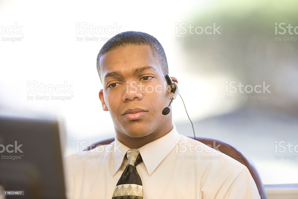 Businessman with a headset working at his computer royalty-free stock photo