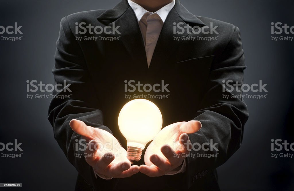 A businessman with a lit lightbulb in his hands royalty-free stock photo