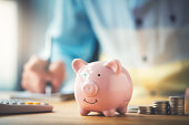 istock Businessman with a piggy bank 1184469841