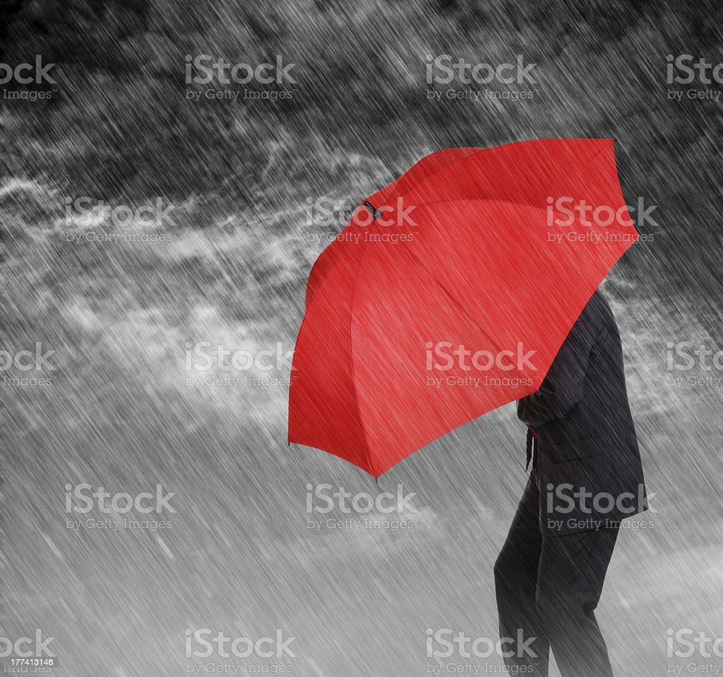 Businessman with a red umbrella sheltering himself from rain stock photo