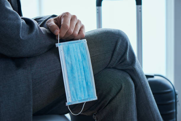businessman with a suitcase and a surgical mask stock photo