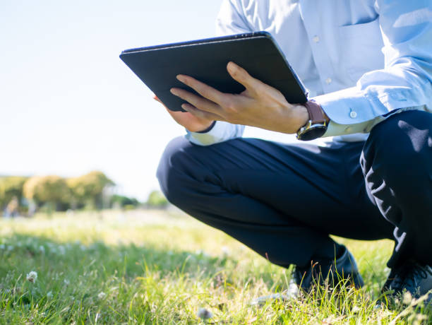 a businessman with a tablet pc in his hand - side hustle stock pictures, royalty-free photos & images