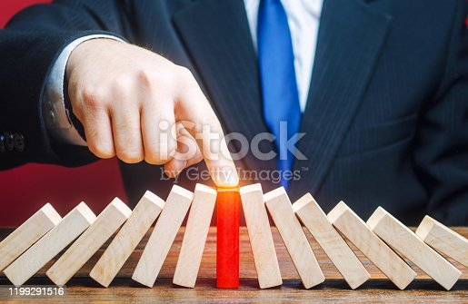 Businessman with a touch stops process of falling dominoes. Risk management concept. Successful strong business, problem solving. Stop destructive processes. Strategy development. Debt restructuring